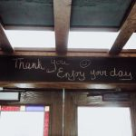 Sign above the exit to the Merchant Taphouse that says 'Thank you, Enjoy your day'